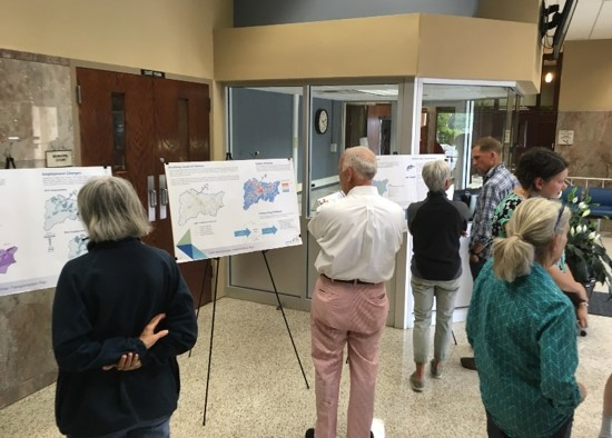 Public meeting inside lobby with display boards